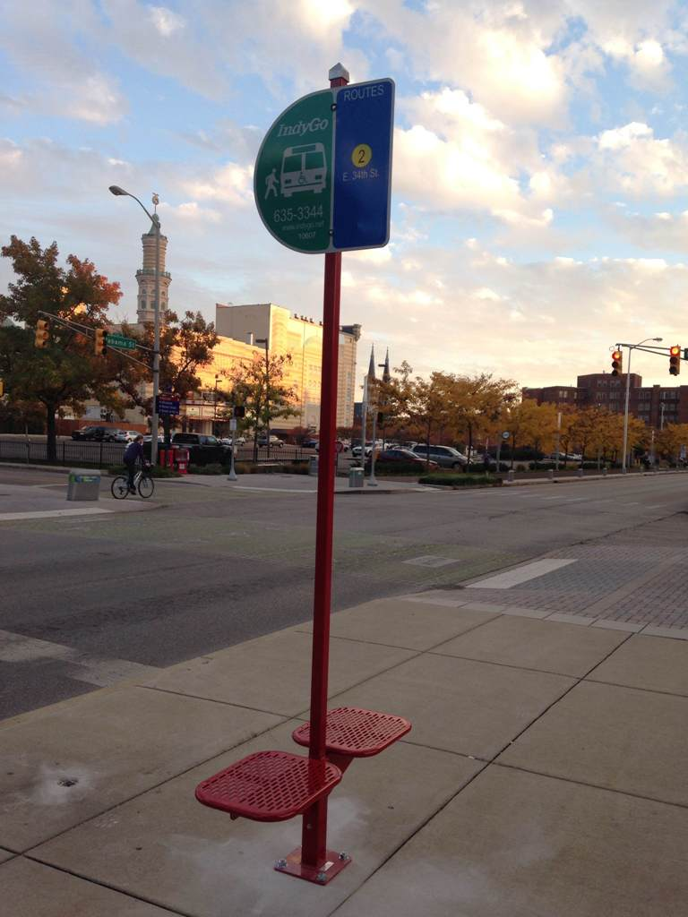 Bus stop sign with small bench. Source: Urban Indy.